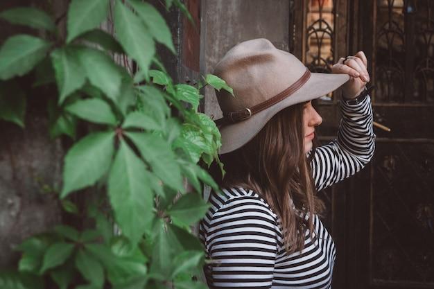 Belle femme dans une chemise rayée tenant son chapeau sur fond de vieille maison et feuilles vertes