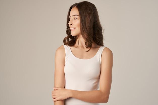 Belle femme dans un fond isolé de soins capillaires tshirt blanc