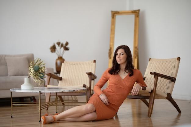 Belle femme dans une longue robe orange est assise sur le sol dans une chambre moderne près d'une chaise en osier