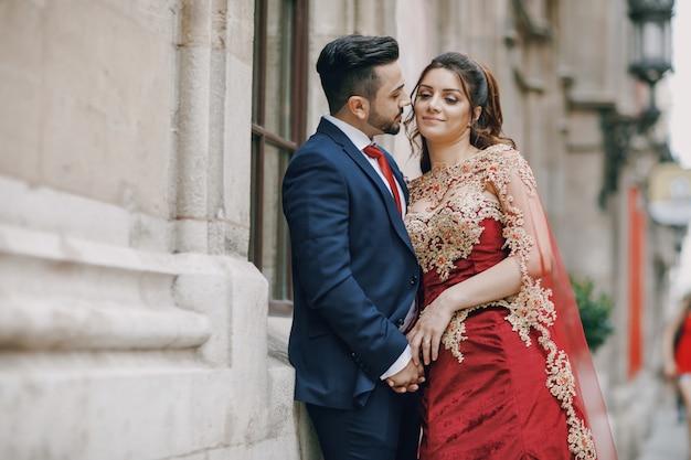 Belle femme dans une longue robe rouge se promène dans la ville avec son mari