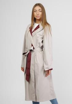 Une belle femme dans un manteau d'automne léger sur fond blanc. photo pour le magasin.