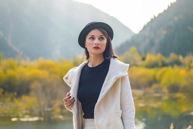 Belle femme dans un manteau blanc et un chapeau noir posant sur un fond de montagnes d'automne