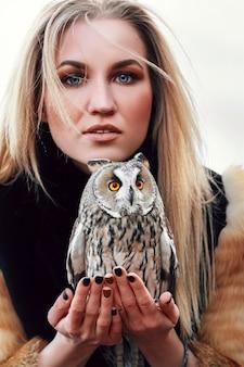 Belle femme dans un manteau de fourrure avec un hibou sur son bras. blonde aux cheveux longs dans la nature tenant un hibou.