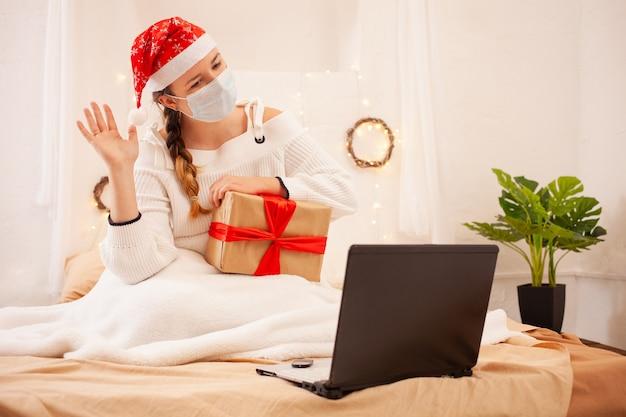 Une belle femme dans un masque et un chapeau de noël félicite ses amis en ligne par appel vidéo