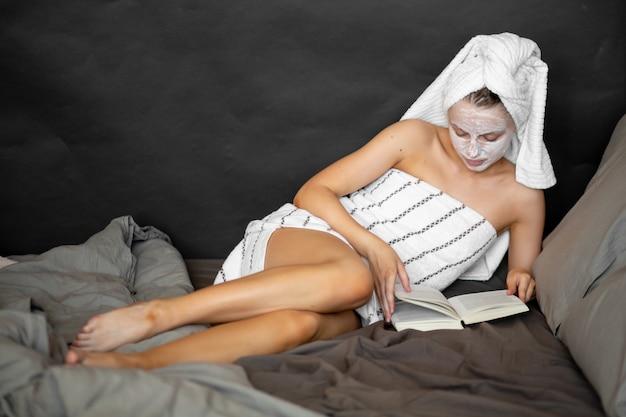 Belle femme dans un masque cosmétique et une serviette tient un verre de champagne, lit un livre au lit et sourit