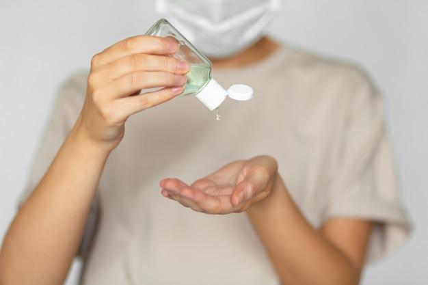 Belle femme dans un masque médical utilise des antiseptiques pour nettoyer ses mains