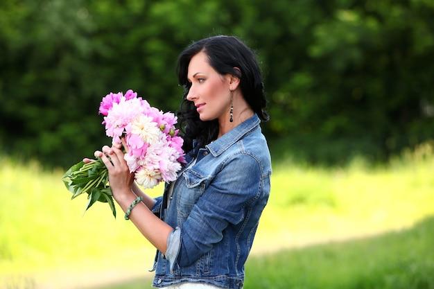 Belle femme dans un parc avec bouquet
