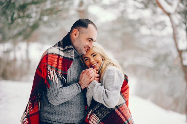 Belle femme dans un parc d'hiver avec son mari