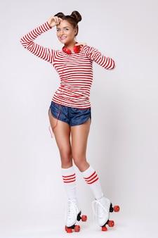 Belle femme dans les patins à roulettes et avec un casque rouge