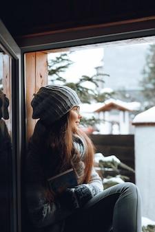 Belle femme dans un pull assis à la maison près de la fenêtre