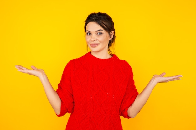 Belle femme dans le pull rouge isolé en studio jaune.