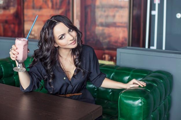 Belle femme dans un restaurant avec un cocktail. modèle heureux avec la boisson dans un sourire en verre transparent
