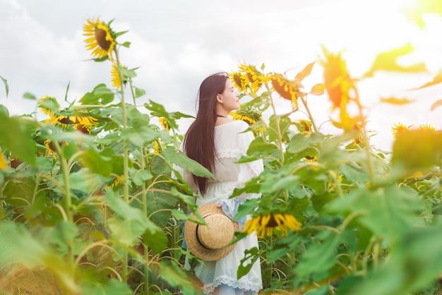 Belle femme dans une robe blanche dans le champ de tournesol