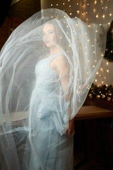 Belle femme dans une robe bleue fermée avec un voile