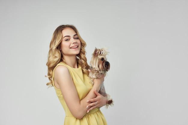 Belle femme dans une robe jaune amusant un petit chien fond isolé