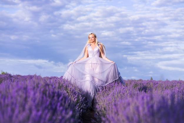 Belle femme dans une robe longue luxuriante court dans un champ de lavande. une fille à l'image d'une fée et d'une princesse de fleurs.