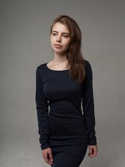 Belle femme dans une robe noire sur gris