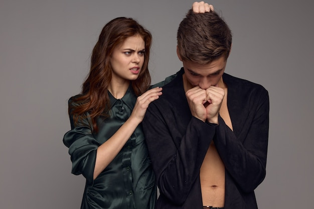 Une belle femme dans une robe sombre calme l'homme bouleversé et lui caresse la tête. photo de haute qualité