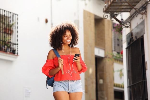 Belle femme dans la rue avec des écouteurs et un téléphone intelligent