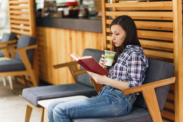 Belle femme dans la rue en plein air café d'été café en bois assis dans des vêtements décontractés, livre de lecture avec une tasse de cocktail