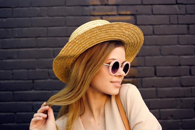 Belle femme dans la rue portant chapeau et lunettes mur de briques noires city trip. photo de haute qualité