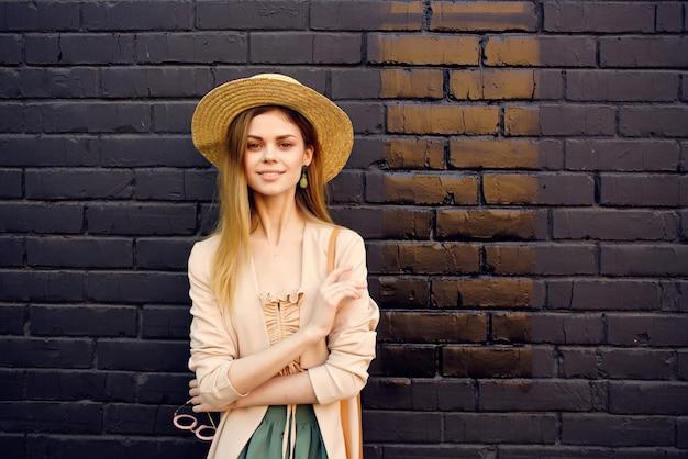 Belle femme dans la rue portant chapeau et lunettes mur de briques noires city trip