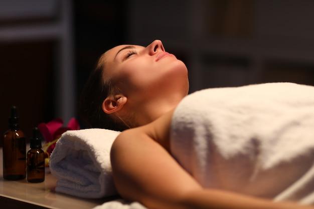 Belle femme dans une serviette se trouve dans une salle de massage