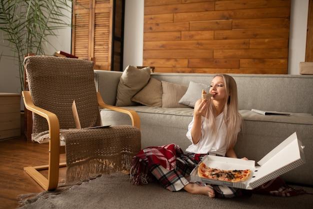 Belle femme dans un t-shirt blanc mange de la pizza avec plaisir assis sur le sol à côté du canapé
