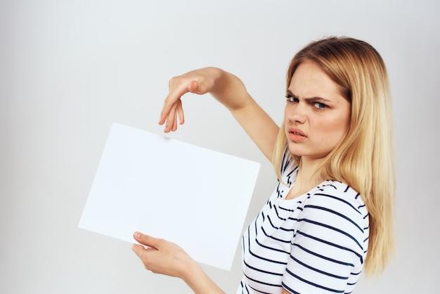 Belle femme dans un t-shirt détient une feuille de papier vierge