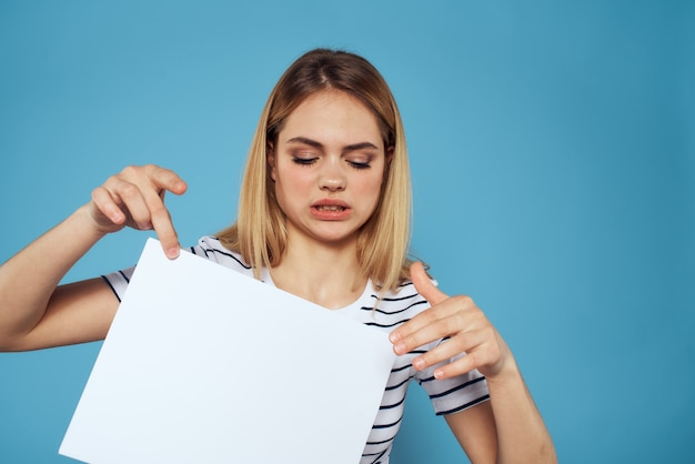 Belle femme dans un t-shirt tient une feuille blanche sans inscription