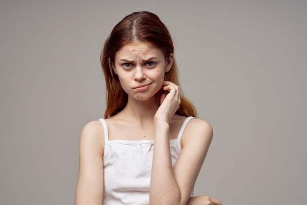 Belle femme dans un tshirt blanc boutons sur le visage fond isolé