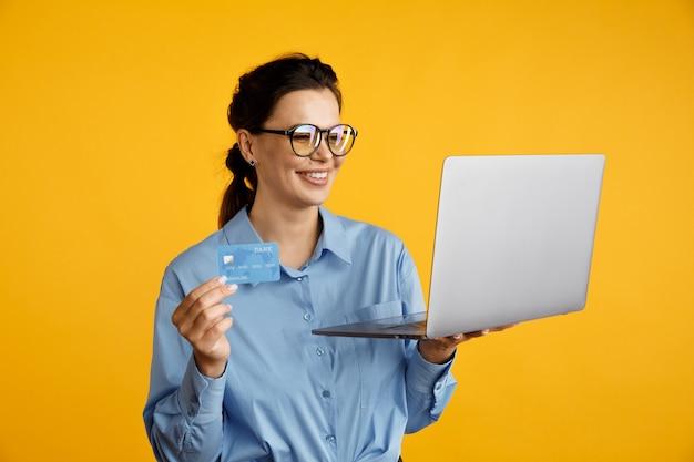 Belle femme dans des verres tenant ordinateur et carte de crédit isolé.