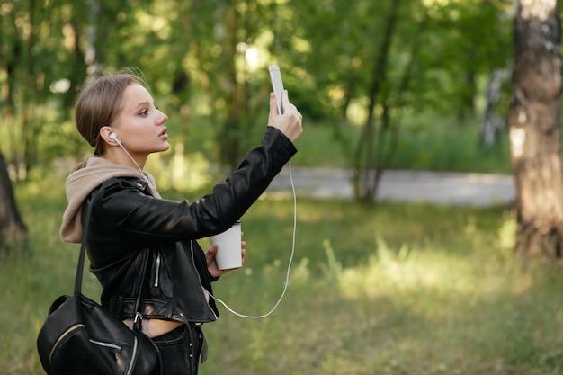 Une belle femme dans une veste en cuir et des écouteurs se promène dans le parc écoute la musique du téléphone et prend un selfie