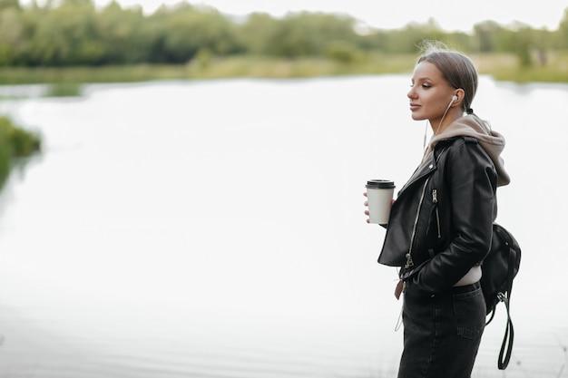 Une belle femme dans une veste en cuir se promène dans le parc avec des écouteurs et boit du café au bord du lac