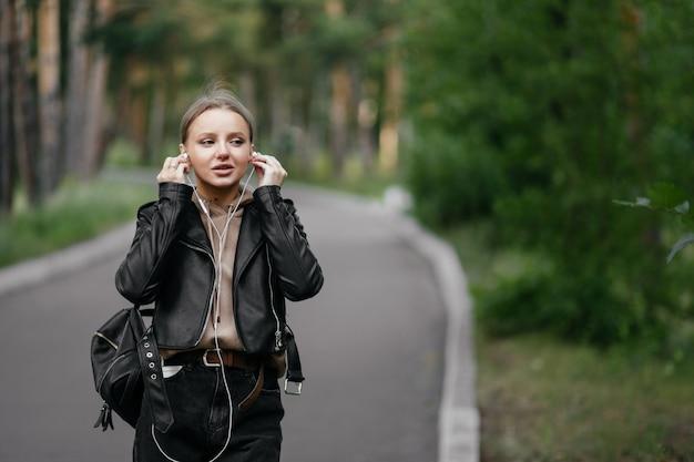 Une belle femme dans une veste en cuir se promène dans le parc, insère des écouteurs dans ses oreilles pour écouter de la musique depuis le téléphone