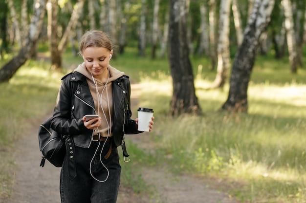 Une belle femme dans une veste en cuir se promène dans le parc