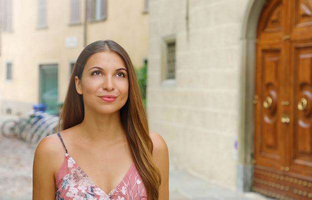 Belle femme dans la vieille ville à la recherche de souhait. copiez la zone d'espace.