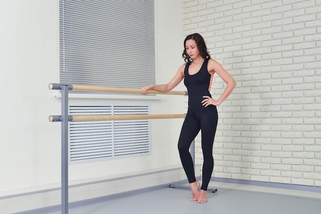 Belle femme danseuse debout détendue neuve près de barre au studio de danse classique