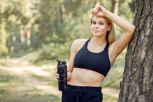 Belle femme debout dans un parc d'été avec de l'eau