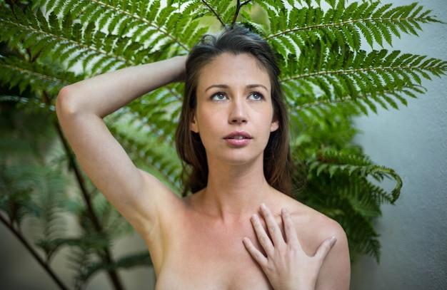 Belle femme debout à l'extérieur contre les plantes vertes