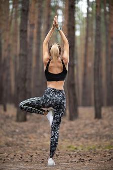Belle femme debout et faire du yoga en forêt. concept d'exercice et de méditation. payez hommage ou soulevez le concept de la main. bois de pin dans le thème de l'été. vue arrière.