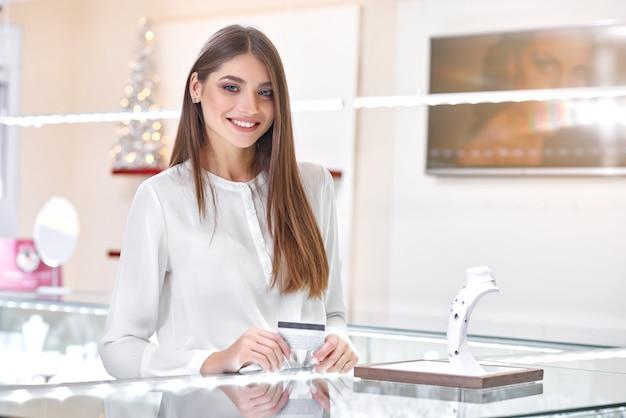 Belle femme debout près du comptoir d'une bijouterie prête à payer pour le collier
