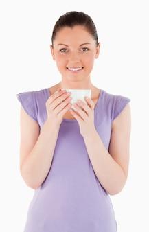 Belle femme dégustant une tasse de café en position debout