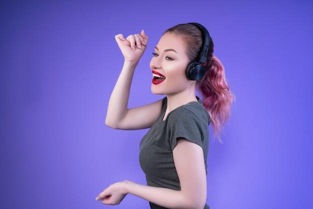 Belle femme à demi tournée avec des lèvres rouges souriant et appréciant la musique
