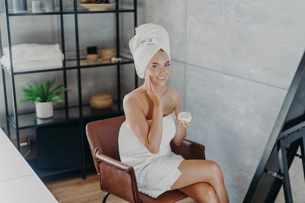 Belle femme détendue enveloppée dans une serviette appliquant la crème pour le visage