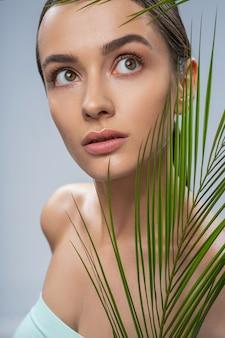 Belle femme détendue avec une feuille de palmier verte