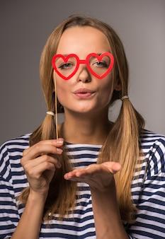 Belle femme avec deux queues tient de fausses lunettes.