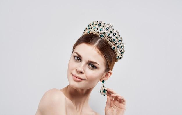 Belle femme avec diadème sur sa tête modèle princesse reine avec portrait de boucles d'oreilles