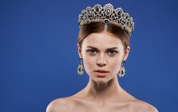 Belle femme avec un diadème sur la tête sur une reine de beauté de mur bleu avec modèle de maquillage de boucles d'oreilles.