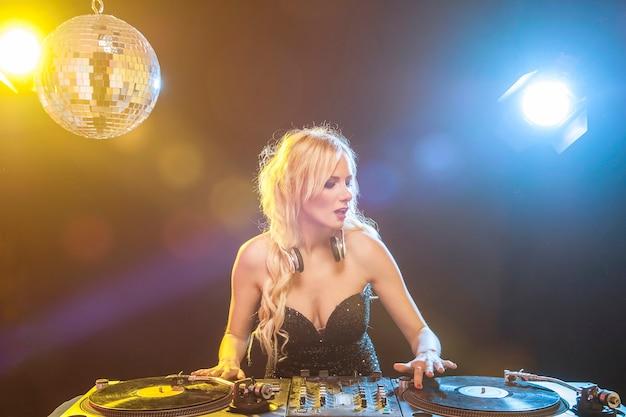 Belle femme dj avec tas de disques vinyles